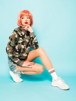Ritratto di cattiva ragazza dei giovani bei pantaloni a vita bassa in vestiti e orecchino rossi d'avanguardia di estate nel suo naso donna sorridente spensierata sexy che si siede nello studio in parrucca rosa vicino alla parete blu divertimento di modello positivo