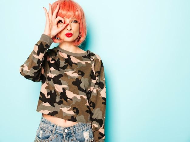 Ritratto di cattiva ragazza giovane e bella hipster in abiti estivi rossi alla moda e orecchini nel naso. donna sorridente spensierata sexy in posa in studio in parrucca rosa. modello copre il suo occhio e mostra segno ok