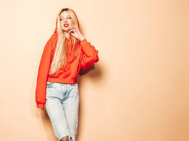 Ritratto di cattiva ragazza giovane e bella hipster in felpa con cappuccio rossa alla moda e orecchini nel naso. modello positivo