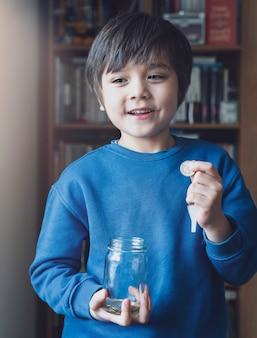 Ritratto di chiave scura di ragazzino che tiene le monete dei soldi in barattolo chiaro, bambino che conta le sue monete salvate, moneta della tenuta della mano di infanzia, bambini che imparano a risparmiare per il concetto futuro