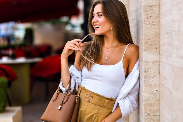 Ritratto di città di stile di vita di incredibile attraente giovane donna bruna che indossa occhiali trasparenti alla moda beige e gioielli in oro, colori caldi morbidi, stile minimalista.