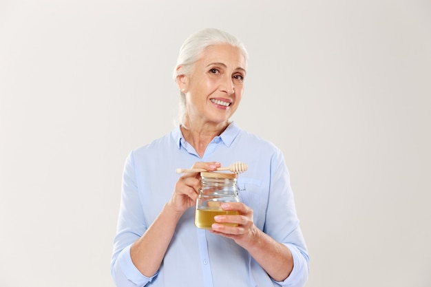 Ritratto di close-up di affascinante donna matura, tenendo il barattolo di miele con cucchiaio