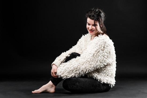 Ritratto di close-up di bella giovane donna con i capelli splendidi e trucco naturale, seduto su un pavimento