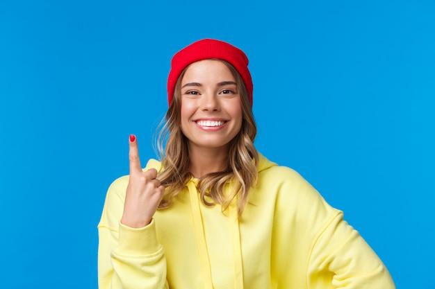 Ritratto di close-up di carina femmina ottimista europea in berretto rosso e felpa con cappuccio gialla, mostrando il numero uno, ordina il tavolo per una persona nella caffetteria, sorridendo felice, in piedi