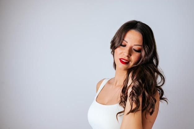 Ritratto di close-up di donna sensuale con capelli ondulati e rossetto rosso. copia spazio
