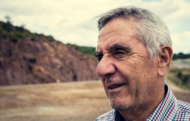 Ritratto di close-up di un anziano uomo sorridente con i capelli bianchi e camicia a quadri