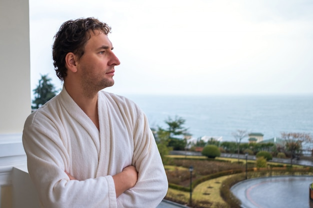 Ritratto di close-up di un uomo in un accappatoio bianco che è in piedi sul balcone dell'hotel con vista sul mare
