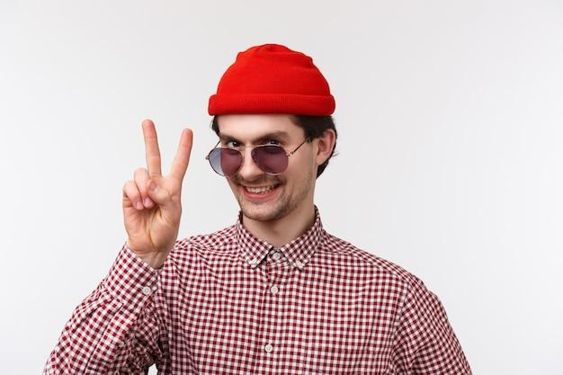 Ritratto di close-up uomo hipster divertente e in uscita in berretto rosso, occhiali da sole e camicia a quadri, preparando le vacanze estive, mostrando il gesto di pace e sorridente, stand muro bianco