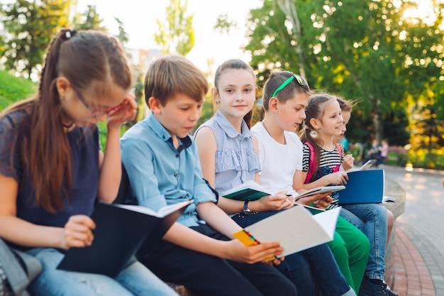 Ritratto di compagni di scuola felice. compagni di scuola posti a sedere con libri in una panchina di legno in un parco cittadino e studiando in giornata di sole.