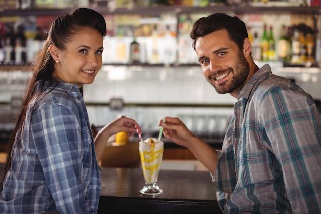 Ritratto di coppia felice con frappè al bancone