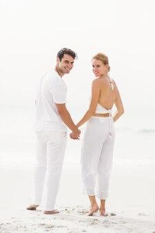 Ritratto di coppia felice in piedi sulla spiaggia