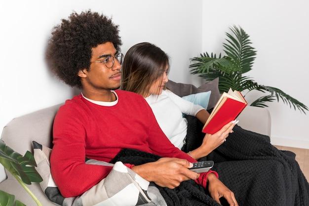 Ritratto di coppia interrazziale leggendo insieme
