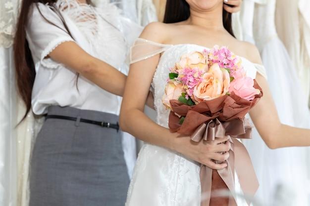 Ritratto di coppia omosessuale asiatica in abito da sposa scegliendo il vestito in un negozio.concept lesbiche lgbt.