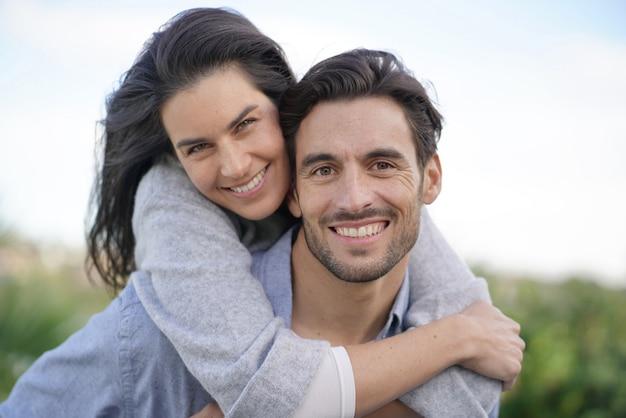 Ritratto di coppia splendida all'aperto che trasporta sulle spalle