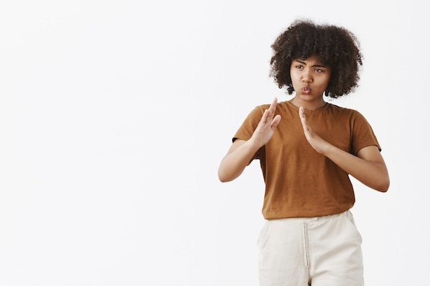 Ritratto di divertente e carino giocoso afroamericano donna dai capelli ricci in t-shirt alla moda alzando le palme in kung fu pongono le labbra pieghevoli sul muro grigio