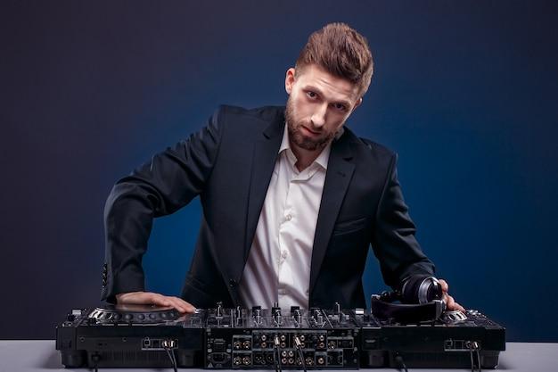 Ritratto di dj fiducioso con stile di capelli alla moda e tavolo di miscelazione