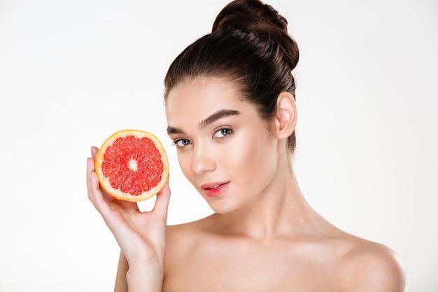 Ritratto di donna abbastanza seminuda con trucco naturale che tiene arancia rossa vicino al suo viso e sguardo