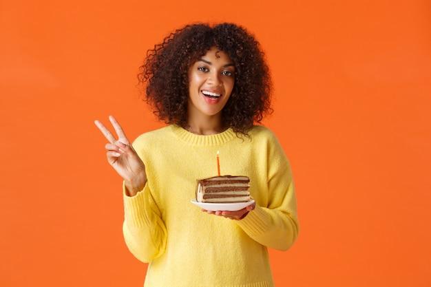 Ritratto di donna afro-americana felice in maglione giallo, che mostra il segno di pace e dire formaggio, ragazza di compleanno che cattura foto con torta b-day e candela, facendo desiderio, in piedi arancione