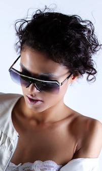 Ritratto di donna afro-americana in abiti eleganti e occhiali da sole