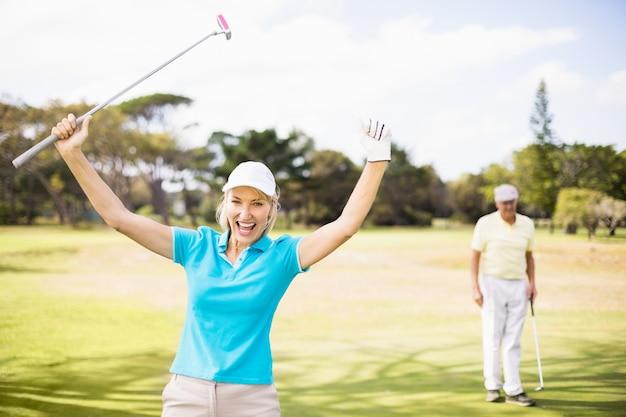 Ritratto di donna allegra golfista con le braccia alzate