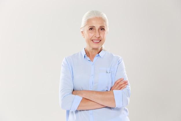 Ritratto di donna anziana felice in piedi con le mani incrociate