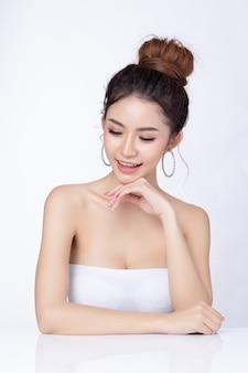Ritratto di donna asiatica attraente seduto sorridente su sfondo bianco.