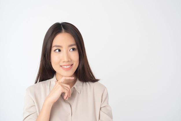Ritratto di donna asiatica attraente sul muro bianco