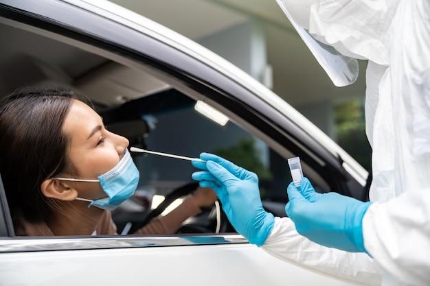 Ritratto di donna asiatica in auto attraverso il test covid-19 del coronavirus da parte di personale medico con tuta dpi con tampone nasale. nuova normale assistenza sanitaria attraverso il servizio e il concetto medico.