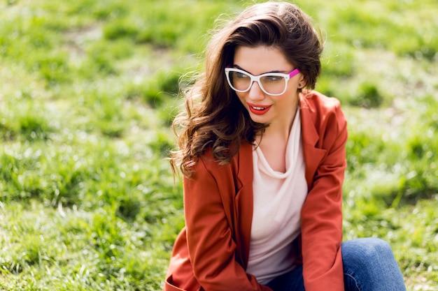 Ritratto di donna attraente con labbra carnose, occhiali da vista, giacca rossa, acconciatura ondulata che si siede sull'erba verde nel soleggiato parco di primavera e sorridente