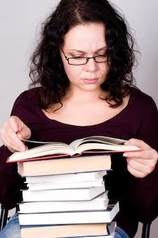 Ritratto di donna attraente con una pila di libri