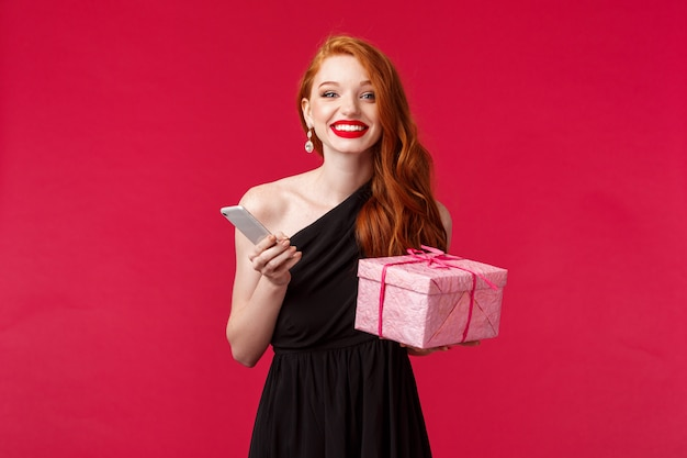 Ritratto di donna attraente felice ed eccitata con i capelli rossi, festeggia il compleanno, vacanze con regali, ricevi regali, scatola di attesa e smartphone ridendo sorridendo, muro rosso
