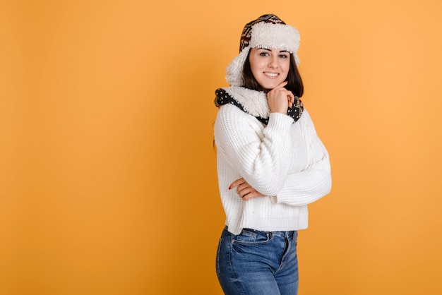 Ritratto di donna attraente in cappello di pelliccia isolato su sfondo arancione