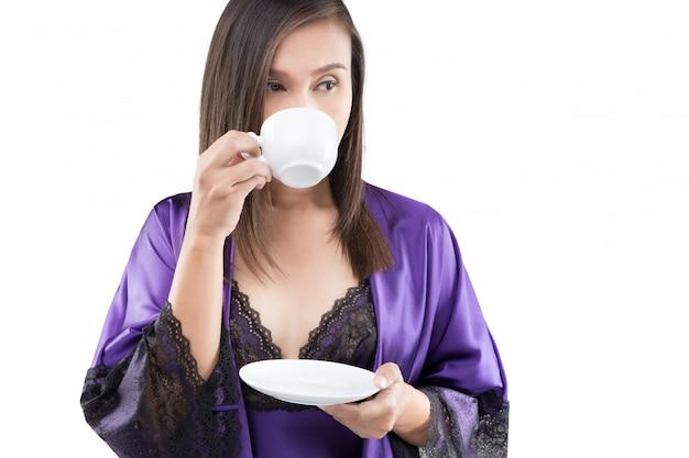 Ritratto di donna attraente in una camicia da notte viola e in possesso di abito di seta