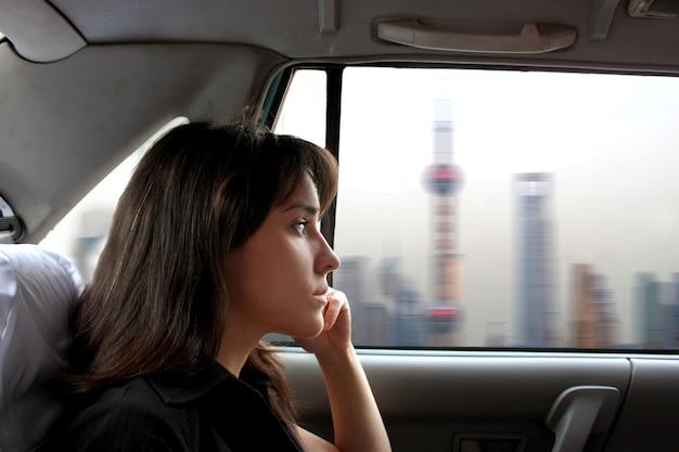 Ritratto di donna attraente, seduto in un taxi e guardando città cinese
