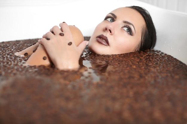 Ritratto di donna bella moda nella vasca idromassaggio con caffè. cura del corpo. trucco luminoso