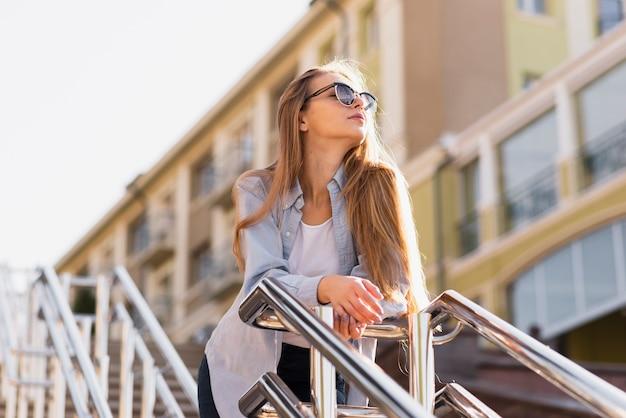 Ritratto di donna bionda che indossa occhiali da sole