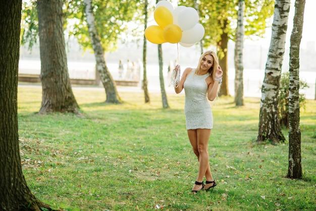 Ritratto di donna bionda che indossa un abito bianco con palloncini a portata di mano contro il parco al addio al nubilato.