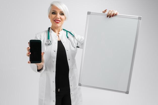 Ritratto di donna bionda in costume di medici con una lavagna magnetica e smartphone nelle sue mani