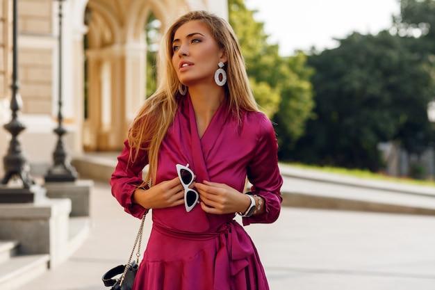 Ritratto di donna bionda seducente in elegante abito di seta