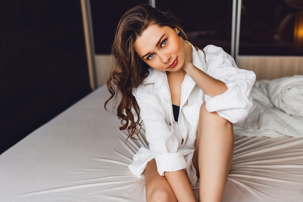 Ritratto di donna bruna in una grande camicia bianca casual che si trova sul suo letto bianco al mattino presto.