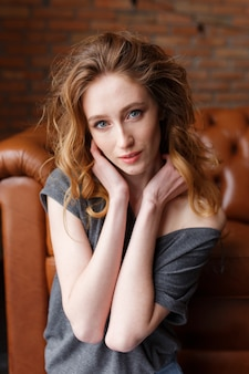 Ritratto di donna capelli rossi. muro di mattoni loft su sfondo. serie