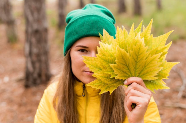 Ritratto di donna che copre il viso con un mazzo di foglie d'autunno