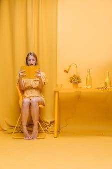 Ritratto di donna che legge un libro in una scena gialla
