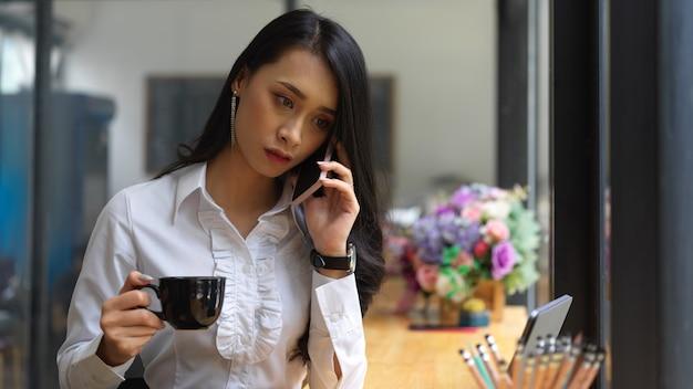 Ritratto di donna che parla al telefono mentre si tiene una tazza di bevanda nella caffetteria