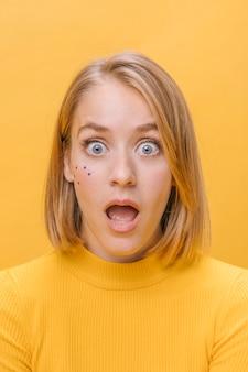 Ritratto di donna con diverse espressioni facciali in una scena gialla