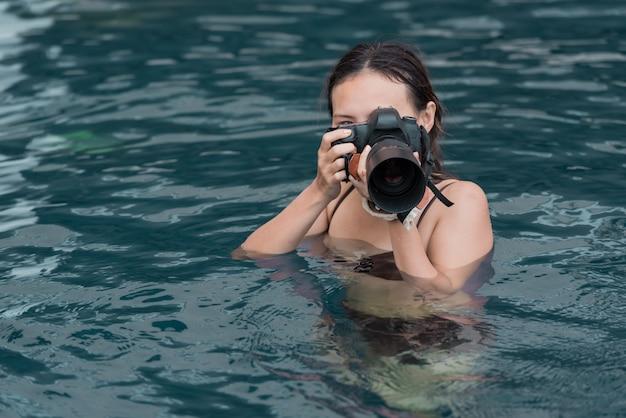 Ritratto di donna con fotocamera dslr scattare una foto in acqua.