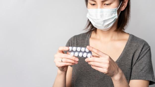 Ritratto di donna con maschera chirurgica controllando compresse