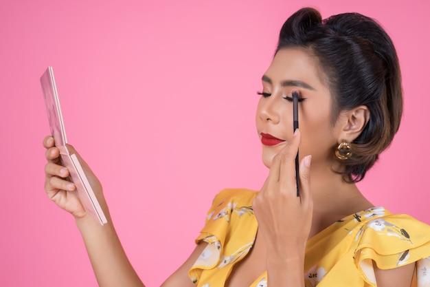 Ritratto di donna con pennello trucco e cosmetici