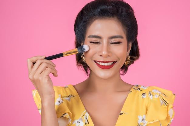 Ritratto di donna con spettacolo professionale pennello trucco