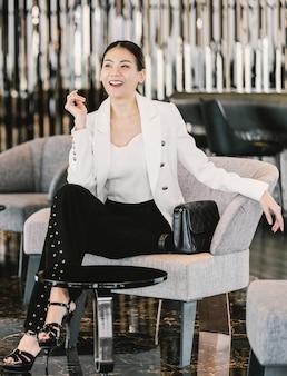 Ritratto di donna d'affari asiatiche che indossa abito formale seduto sul divano nella moderna hall, ufficio o spazio di coworking, pausa caffè per il tempo libero, moda e stile di vita dopo l'orario di lavoro, concetto di uomini d'affari